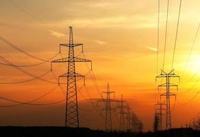 eine Reihe von Stromleitungen während des Sonnenuntergangs foto