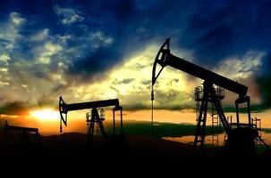 Ölpumpen arbeiten am Sonnenunterganghintergrund foto