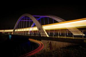 Eisenbahnbrücke mit Zug- und Autolichtern bei Nacht foto