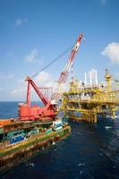 großes Kranschiff, das die Plattform vor der Küste installiert foto