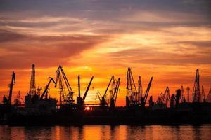 schwarze Silhouetten von Kränen und Frachtschiffen im Hafen von Varna