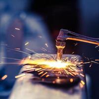 Arbeiter schneiden Stahlrohr mit Metallbrenner und installieren Straßenrand foto