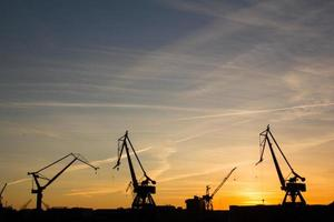 Hafenkräne bei Sonnenuntergang foto