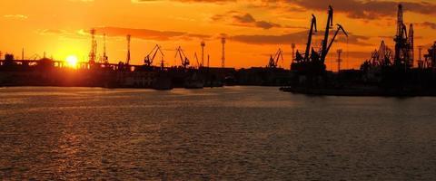 lebendiger Sonnenuntergang am Frachtseehafen foto