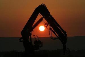 Sonnenuntergang mit Hebezeug im Vordergrund foto