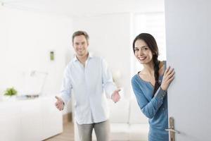 fröhliches Paar, das Leute einlädt, nach Hause einzutreten
