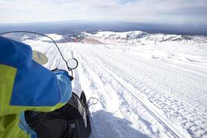 Menschen auf Schneemobil im Winterberg foto