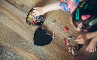 Baby spielt mit Haarspangen, die im Boden sitzen foto