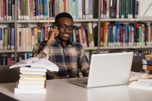 männlicher Student, der am Telefon in der Bibliothek spricht foto