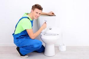 Klempner mit Toilettenkolben auf hellem Hintergrund foto
