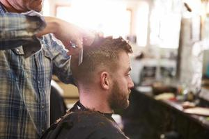 männlicher Friseur, der Kundenhaarschnitt im Geschäft gibt foto