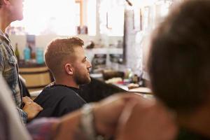 männlicher Friseur, der dazu neigt, Kunden im Laden zu machen foto