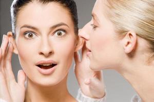 Frau flüstert einer anderen Frau ein Geheimnis zu, die schockiert aussieht foto