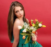 schönes Mädchen in einem Sommerkleid mit Tulpen