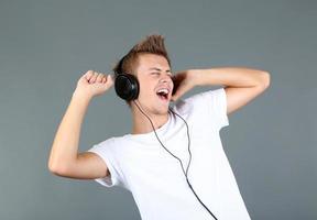 schöner junger Mann, der Musik auf grauem Hintergrund hört foto