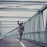 hübsches Mädchen, das glücklich auf einer Brücke geht foto