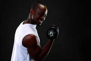 lächelnder afrikanischer Mann mit Hanteln foto