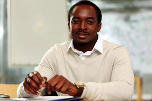 glücklicher afrikanischer Mann, der am Tisch sitzt foto