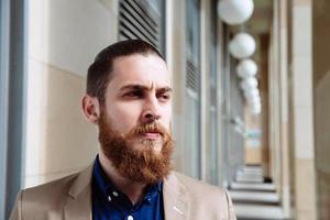 bärtiger Hipster, der Hemd in der Stadt trägt foto