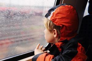sieben Jahre alter Junge, der im Zug sitzt foto