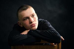 junger, trauriger Mann in der schwarzen Kleidung foto