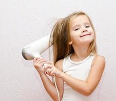 süßes lächelndes kleines Mädchen trocknet Haare foto