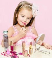 süßes kleines Mädchen der Kinderkosmetik mit Lippenstift