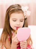 kleines Mädchen mit Lippenstift und Spiegel