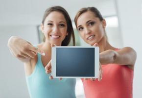 fröhliche Mädchen, die eine Tafel zeigen foto