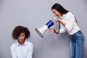 Frau schreit durch Lautsprecher auf ihre Freundin foto