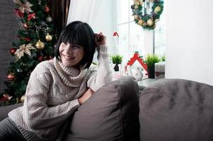 lächelnde Brünette sitzt auf der Couch foto