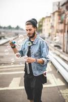 junger hübscher bärtiger Hipster-Mann, der Seifenblasen bläst foto