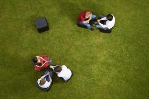 Leute, die auf Stühlen im Gras sprechen foto