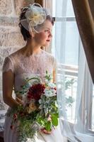 junge und attraktive Braut, die am Fenster sitzt foto