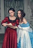 schöne Mädchen in mittelalterlichen Kleidern mit Schriftrollenbuchstaben foto