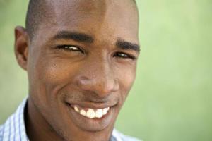 Porträt des glücklichen jungen Mannes, der Kamera betrachtet und lächelt foto