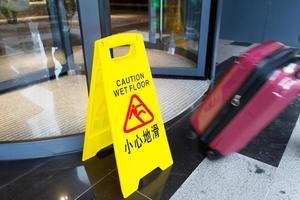 Schild mit der Warnung vor Vorsicht auf nassem Boden foto