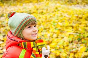 glücklicher Junge, der im Herbstpark lächelt foto