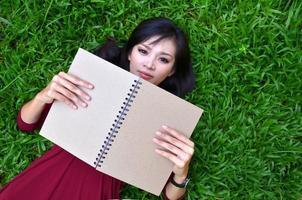 Frau, die auf grünem Gras mit Buch liegt foto