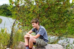 junger Teenager, der auf einem Bergfelsen sitzt foto