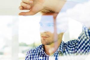 hübscher junger Mann, der durch das Fenster schaut und denkt foto