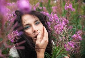 schönes Mädchen unter den Blumen foto