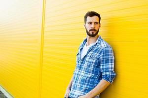 junger hübscher Mann mit Kopfhörern auf gelber Wand foto