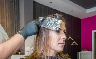 Friseurhände, die Frauenhaar mit Aluminiumfolie einwickeln foto