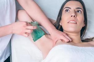 Kosmetikerhände, die Enthaarung in der Achsel der Frau mit Wachsstreifen tun foto