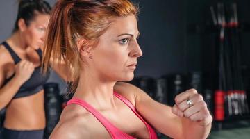 Frau, die hartes Boxen im Fitnessstudio trainiert foto