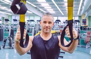 Mann macht Suspensionstraining mit Fitnessgurten foto