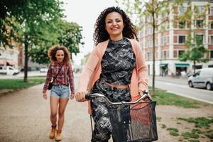 glückliche junge Frau, die Fahrrad auf Stadtstraße reitet foto
