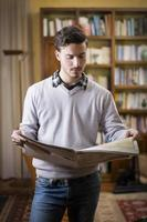 hübscher junger Mann, der zu Hause Zeitung liest foto