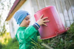 Porträt eines kleinen Jungen, der ein Gras wegwirft